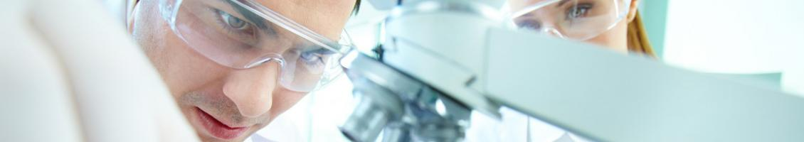 Man wearing safety glasses looking at microscope