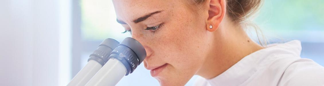 Woman looking down a microscope