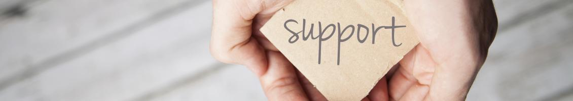 Cupped hands holding a piece of paper with support written on it